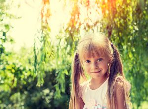 Portrait of smiling little girl in the park in summer
